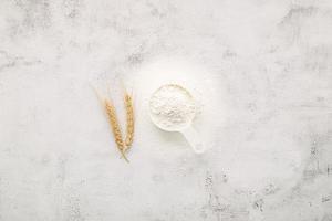 farina di frumento in ciotola di legno allestita su sfondo di cemento bianco foto