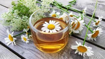 primo piano aromatico del tè alla camomilla in una tazza di vetro su un fondo di legno. foto