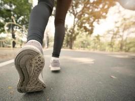 close up scarpe da corsa e gamba del corridore nel parco foto