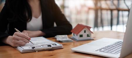 vista ravvicinata mani di una donna d'affari che firma una casa in leasing foto
