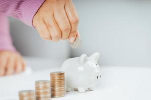 mano della donna che mette la moneta dei soldi nel salvadanaio per risparmiare denaro. foto