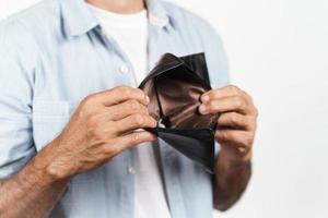 uomo che tiene il suo portafoglio vuoto su sfondo bianco. senza soldi. foto