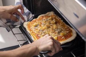 mani di donna che tirano fuori la pizza dal forno foto