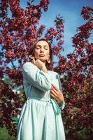 una giovane ragazza è in piedi nel parco sotto un melo in fiore foto