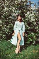 la ragazza si siede nel parco sull'erba sotto un melo bianco in fiore foto