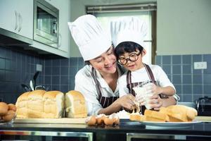 donna asiatica e ragazzo con gli occhiali che cucinano foto