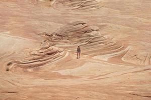donna che cammina su una formazione rocciosa di arenaria nel deserto foto