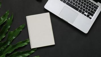 vista dall'alto notebook foglia laptop su sfondo nero foto