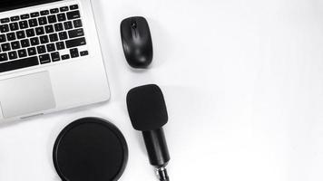 vista dall'alto del tavolo con notebook, microfono, mouse e tastiera foto