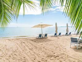 all'aperto con ombrellone e sdraio sulla bellissima spiaggia tropicale e mare foto