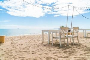 sedie bianche e tavolo sulla spiaggia con vista sull'oceano blu e sul cielo limpido foto