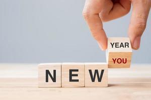 blocco di capovolgimento a mano con il nuovo anno per il nuovo testo foto