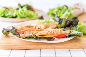 avvolgere il rotolo di insalata sul tavolo foto