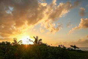 surfista che cammina al tramonto alle hawaii foto