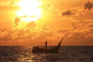 un pescatore sta pregando con un bellissimo sfondo del tramonto foto