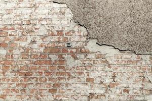 fondo del muro di mattoni del grunge con stucco frastagliato foto