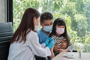 dottoressa che vaccina una ragazza asiatica presso la clinica pediatrica. foto