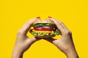 persona che tiene un delizioso hamburger vegetariano. foto
