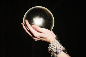 le mani dell'indovino su un globo di vetro su sfondo nero. foto