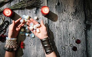 mani dell'indovino con rune di pietra, interno mistico. foto