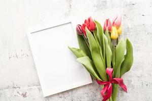 bouquet di tulipani e cornice vuota per il design mock up su sfondo bianco foto