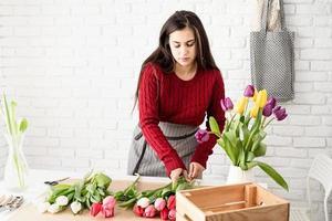 fiorista donna che fa un mazzo di tulipani freschi e colorati foto