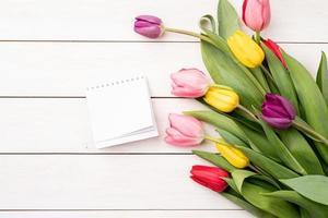 vista dall'alto del calendario vuoto con tulipani colorati su sfondo bianco foto