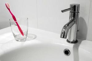 rubinetto del bagno e lavabo con bicchiere d'acqua e spazzolino da denti foto