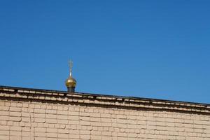 la cupola della chiesa dietro il muro di mattoni. foto