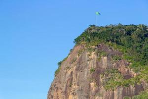 Timone in pietra con bandiera brasiliana in cima, visto dalla spiaggia di timone a rio de janeiro, brasile foto