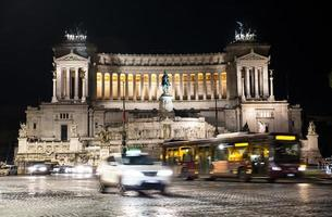 piazza venezia con veicoli in movimento a roma, italia di notte foto