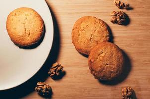 biscotti con noci su un piatto e un tavolo foto