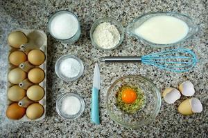 uova, latte e altri prodotti sul tavolo della cucina. foto