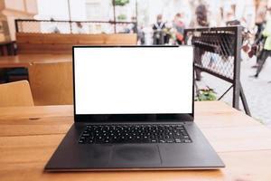 schermo del computer portatile bianco sul tavolo in un caffè per strada foto