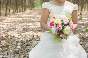 sposa che tiene grande bouquet da sposa nella foresta. foto