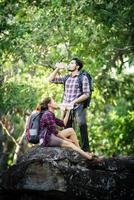 giovane coppia che cammina con gli zaini nella foresta. escursioni avventurose. foto
