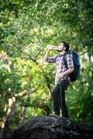 giovane escursionista che si rilassa in cima a una montagna, si gode la natura e l'avventura foto