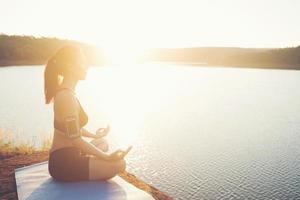 la giovane donna in buona salute sta praticando lo yoga al lago di montagna durante il tramonto. foto
