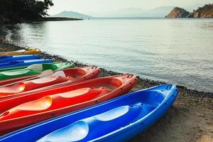 colorate barche in canoa sulla spiaggia, mare e montagne sullo sfondo foto