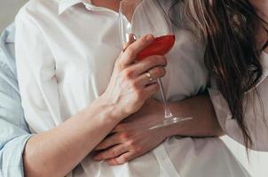 una giovane coppia con vino rosato che si abbraccia foto