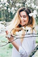 una bella ragazza gode di alberi di magnolia in fiore, i suoi lunghi capelli in movimento foto