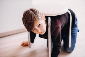un bambino carino gioca sul pavimento fingendo di essere una tartaruga foto