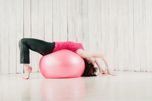 una ragazza in un top rosa, che fa un ponte su un fitball rosa in una palestra foto