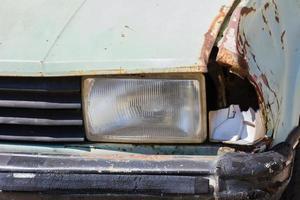 primo piano di un'auto rottamata lasciata in un parcheggio foto