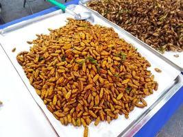 Insetti fritti baco da seta croccante venduto nel mercato di strada, Thailandia foto
