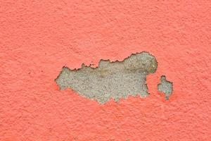 vecchia vernice e muro, muro screpolato di colore arancione. foto