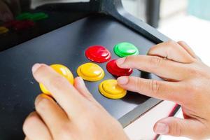 mani ravvicinate che premono e tengono premuto il joystick del vecchio videogioco arcade foto