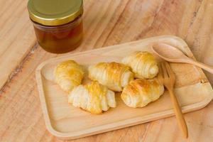piccoli gustosi croissant sul piatto di legno vicino a cucchiaio e forchetta foto