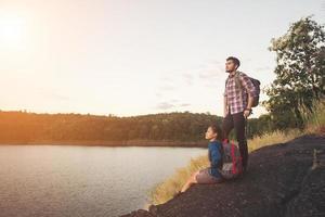 coppia che si riposa sulla cima della montagna sotto il lago durante il tramonto. foto