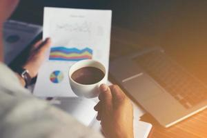 grafico finanziario di analisi dell'uomo d'affari e tenendo una tazza di caffè. foto
